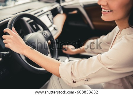 Cropped image of beautiful young woman driving a car and smiling #608853632