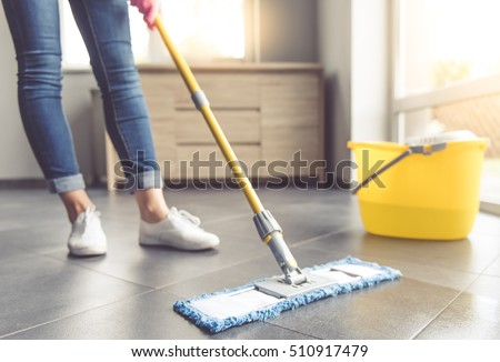 Cropped image of beautiful young woman in protective gloves using a flat wet-mop while cleaning floor in the house Stock foto ©