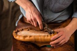 Cropped image of bootmaker sitting in workshop making shoes