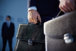 Cropped image of business partners carrying briefcases on the foreground while their colleague standing on the background