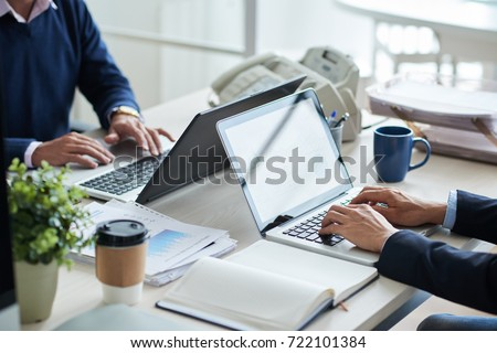 Cropped image of business people working on laptops in office