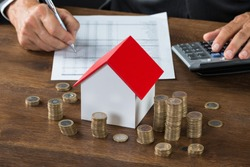 Cropped image of businessman calculating tax by model house and stacks of coins on table