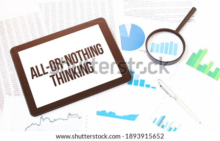 Cropped image of businessman examining graph on digital tablet with magnifying glass at office desk. Text ALL-or-NOTHING THINKING Stock photo ©