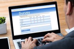 Cropped image of businessman giving online survey on laptop at office desk