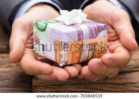 Cropped image of businessman holding gift box made from euro papernotes at wooden table