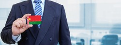 Cropped image of businessman holding plastic credit card with printed flag of Belarus. Background blurred.