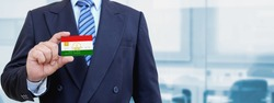 Cropped image of businessman holding plastic credit card with printed flag of Tajikistan. Background blurred.