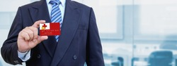 Cropped image of businessman holding plastic credit card with printed flag of Tonga. Background blurred.