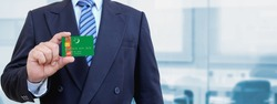 Cropped image of businessman holding plastic credit card with printed flag of Turkmenistan. Background blurred.