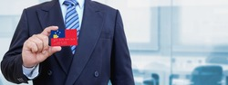Cropped image of businessman holding plastic credit card with printed flag of Western Samoa. Background blurred.
