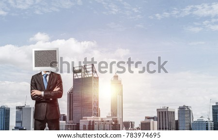 Cropped image of businessman in suit with monitor instead of head keeping arms crossed while standing outdoors with cityscape view on background. #783974695