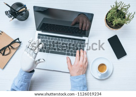 cropped image of businessman with prosthetic arm using laptop at table with potted plant and cup of coffee  Stock photo ©