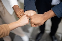 Cropped image of businessteam bumping fists each other on city street. Concept of modern successful business people. Idea of business cooperation. Remote and freelance work. Close up view