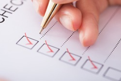 Cropped image of businesswoman writing on checklist