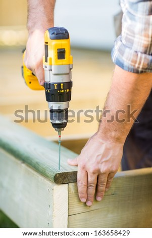 Cropped image of carpenter's hands using drill on wood at construction site