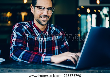 Photo of Cropped image of cheerful graphic designer in optical spectacles working on creating new project and development website using free 4G internet connection on modern laptop computer in cafe indoors