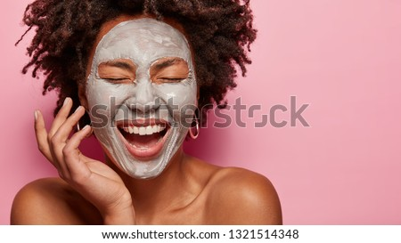 Cropped image of cheerful pleased young African American woman has deep cleansing nourishing face mask, shows bare shoulders, isolated over rosy background with blank space for your promotion.