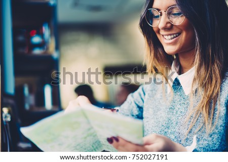 Photo of Cropped image of cheerful smart student in stylish optical eyeglasses laughing during studying while sitting indoors in coffee shop interior.Copy space area for your advertising text message