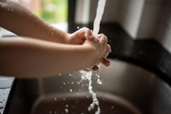 Cropped image of child washing his hands. Water splashes all around. Virus spread prevention