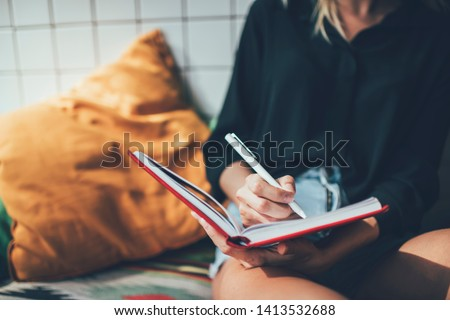 Photo of Cropped image of clever female student writing ideas for university course work using notepad for education, smart hipster girl making notes of thoughts in personal diary during leisure time