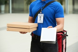 Cropped image of courrier giving you digital tablet to sign for the pizza delivery