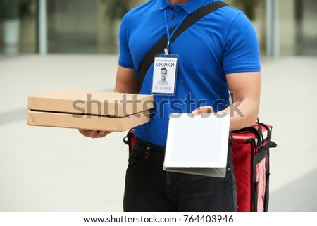 Cropped image of courrier giving you digital tablet to sign for the pizza delivery Photo stock ©