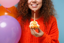 Cropped image of cute young african american girl in orange knitted clothes isolated on pastel blue background. Birthday holiday party concept. Celebrating hold colorful air balloons cake with candle