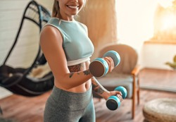 Cropped image of determined woman losing weight at home and exercising with dumbbells. Sport and recreation concept. Beautiful woman in sportswear with blue dumbbells in her hands.