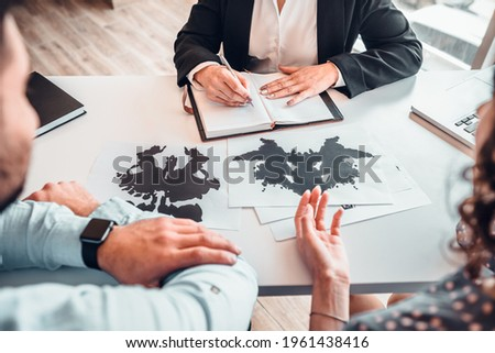Cropped image of family sitting on psychology consultation on the desk, passing rorschach test with help of female psychotherapy specialist. Diagnosis disorders, depression, stress concept