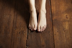 Cropped image of female bare feet on a wooden floor