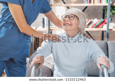 Cropped image of female caretaker helping senior woman to walk with walker at home Stock photo ©