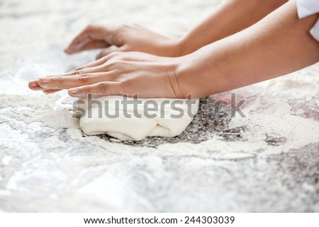 Cropped image of female chef\'s hands kneading dough at messy counter in commercial kitchen