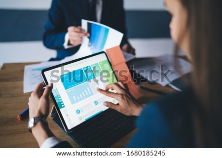Cropped image of female professional checking financial website with revenue statistics and marketing infographics, expert woman browsing web page with graph charts of corporate monetary gain