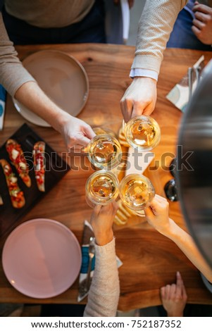 Cropped image of four friends cheering with wine