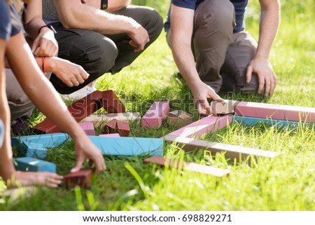 Cropped Image Of Friends Playing With Building Blocks On Field #698829271