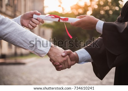 Cropped image of graduate in academic dress taking his diplomas and shaking hand
