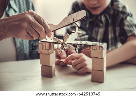 Cropped image of grandpa and grandson playing with toys while resting together at home