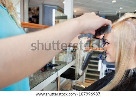 Cropped image of hairstylist combing hair of young female customer before haircut at salon
