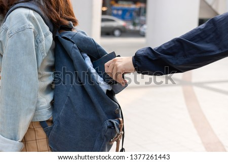 Cropped image of hands of pickpocket thief stealing wallet from backpack of tourist girl Сток-фото ©