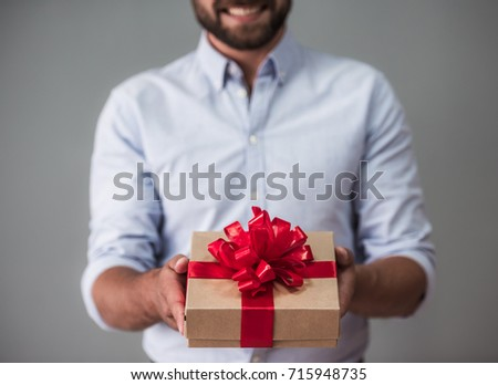 Cropped image of handsome bearded man in smart casual wear holding a gift box and smiling, on gray background