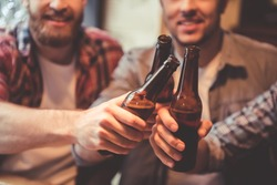 Cropped image of handsome friends clinking bottles of beer and smiling while resting at the pub