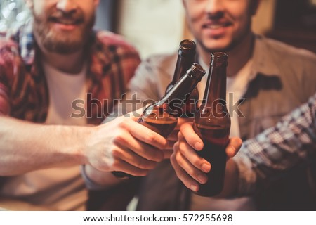Cropped image of handsome friends clinking bottles of beer and smiling while resting at the pub #572255698