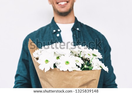 Cropped image of handsome male with a bunch of flowers preparing for a date with girlfriend. Young happy man smiling and delivering a bouquet of white flowers posing on white wall.