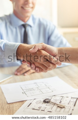 Cropped image of handsome middle aged realtor in classic shirt shaking hands with his clients and smiling while sitting in office