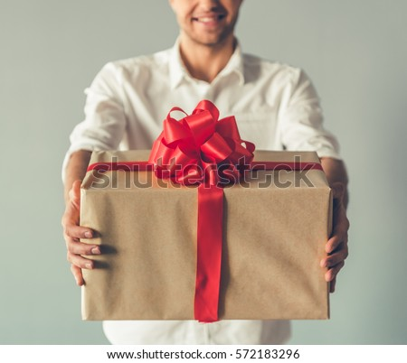 Cropped image of handsome romantic guy smiling while holding a big gift box for his couple, on gray background