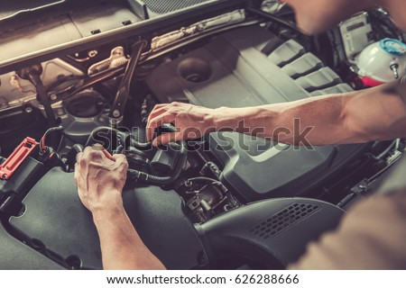Cropped image of handsome young auto mechanic in uniform repairing car in auto service
