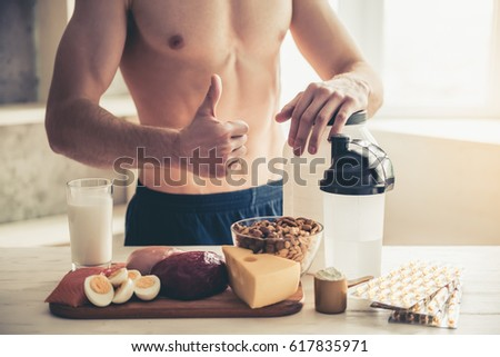 Cropped image of handsome young sportsman showing Ok sign while preparing sport nutrition in kitchen at home #617835971