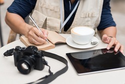 Cropped image of journalist making notes while sitting in the cafe