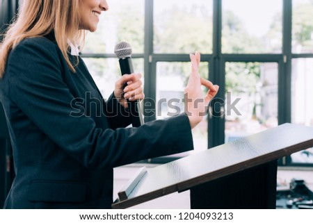 cropped image of lecturer showing okay gesture at podium tribune during seminar in conference hall