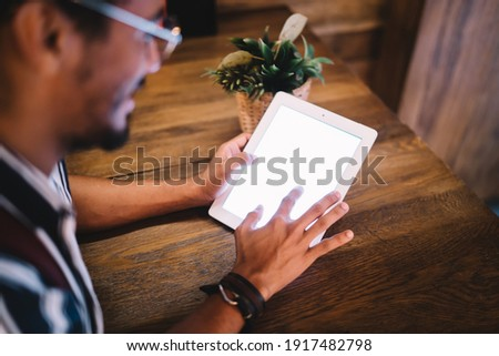 Photo of Cropped image of male african american reading web page information on digital tablet with mock up screen, dark skinned hipster guy typing on touchpad with black monitor sitting in cafe on free time
